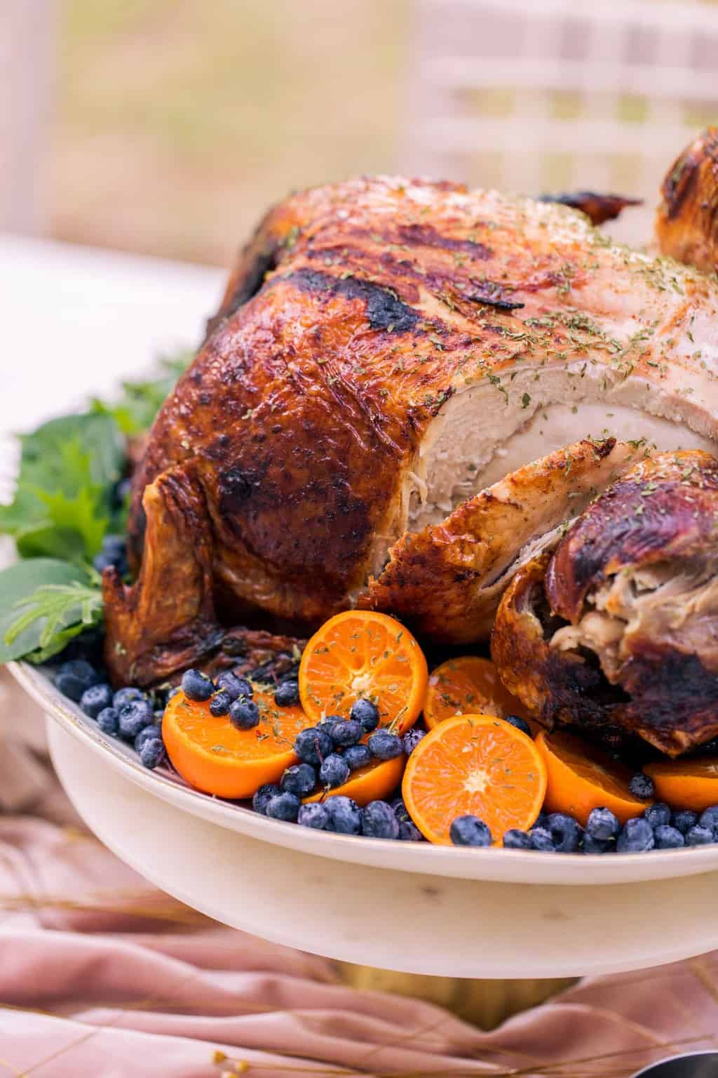 close up photo of a sliced thanksgiving turkey recipe with citrus and berries