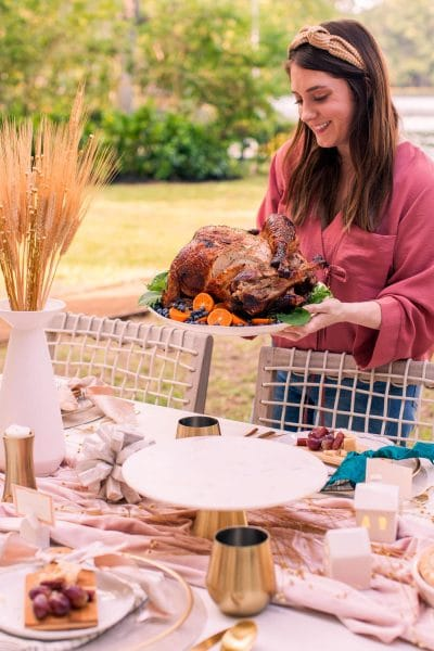 a girl holding a plated air fryer turkey recipe by a thanksgiving table
