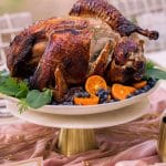 photo of a sliced thanksgiving air fryer turkey with berries and greens