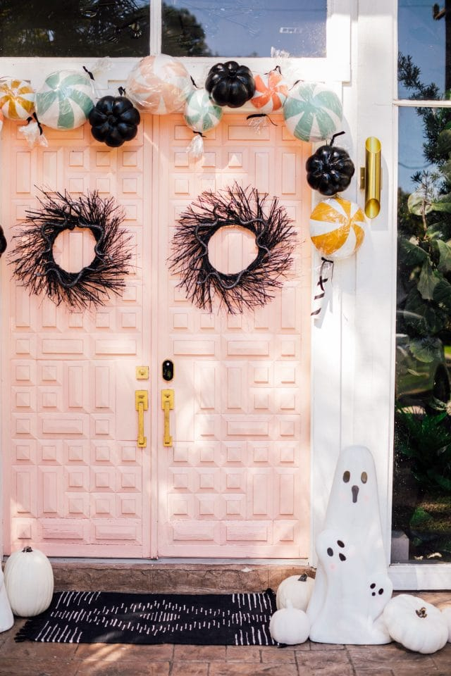 pink front door with two black wreath and ghost