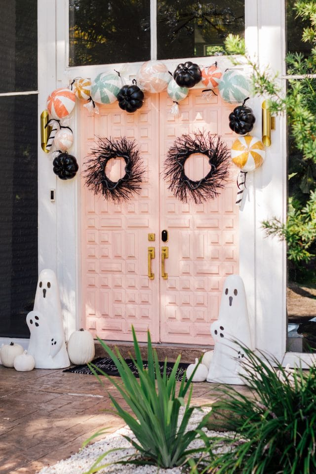 angle view of a pink front door with halloween door decor