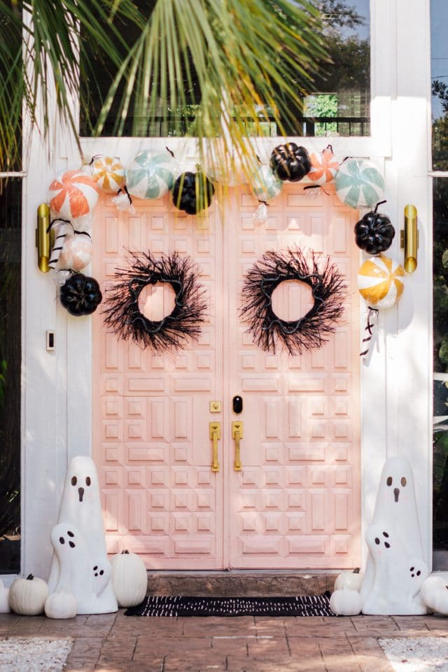 two black wreaths and a pink double door with ghost decorations