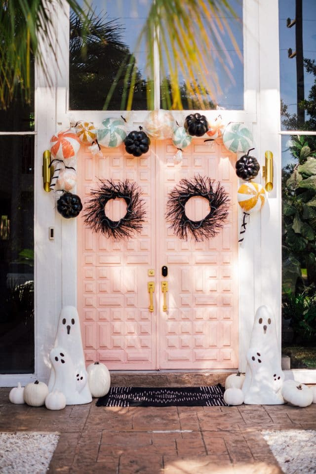 pink front door with halloween candy and ghost decorations