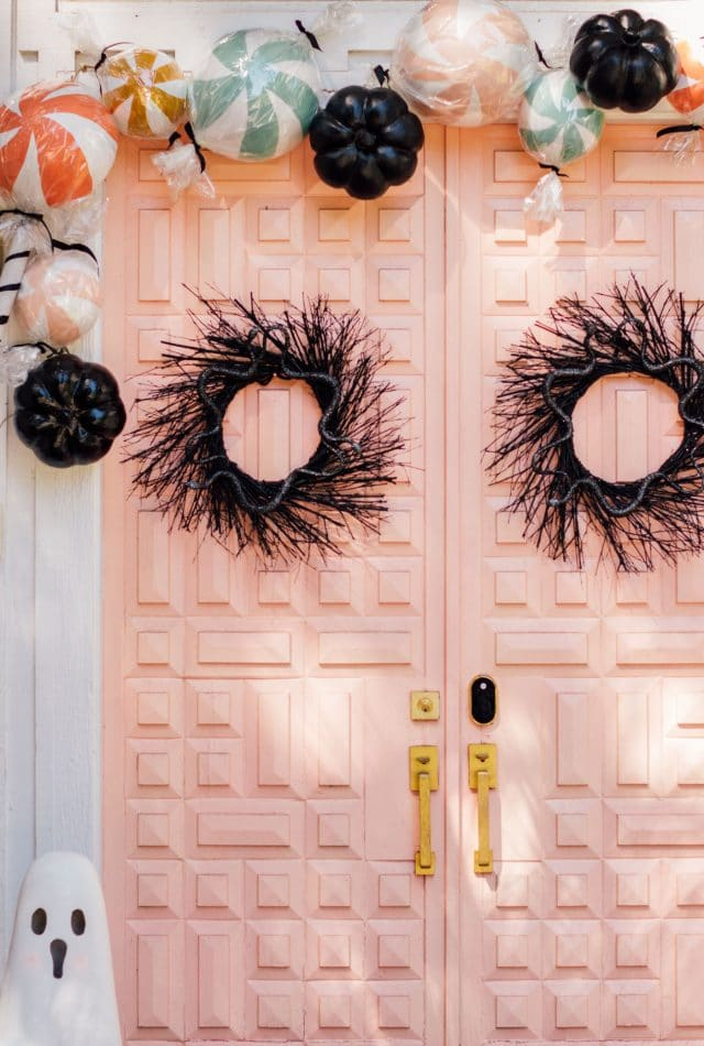 black front door wreaths on a pink door