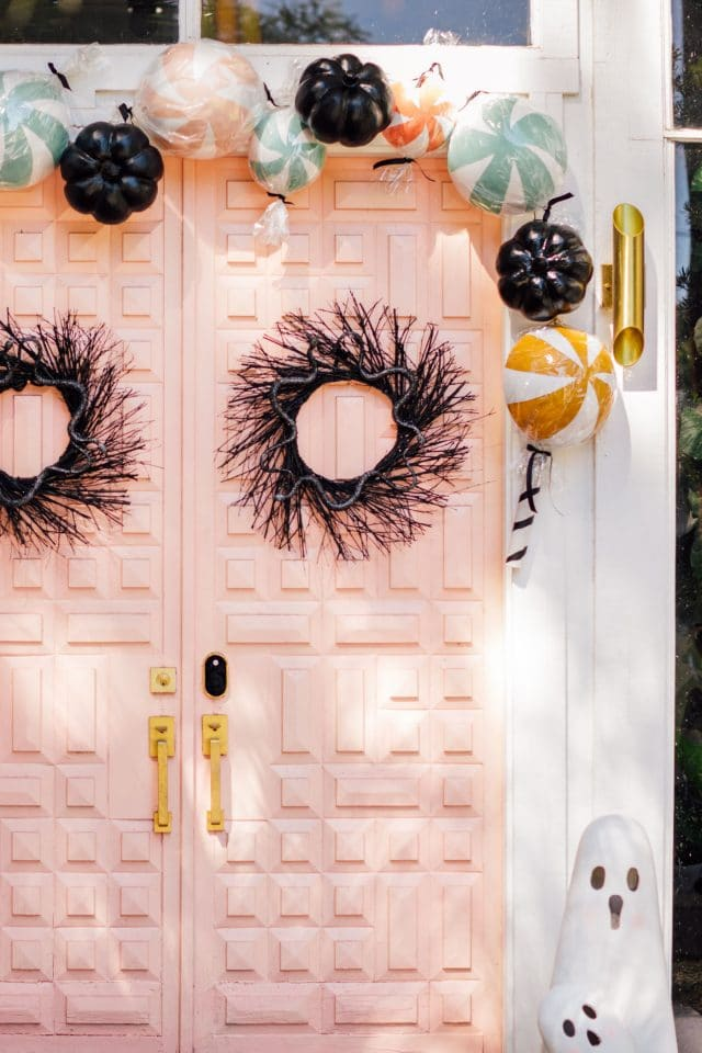 pink door with fake candy decorations and a ghost