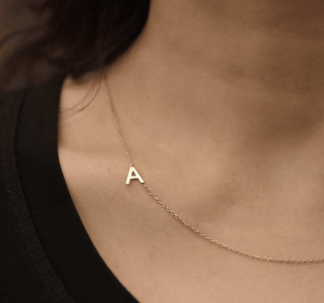 close up of woman wearing a gold initial necklace as a personalized gift for girls idea