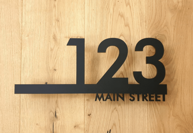 photo of a metal address sign on a wooden wall