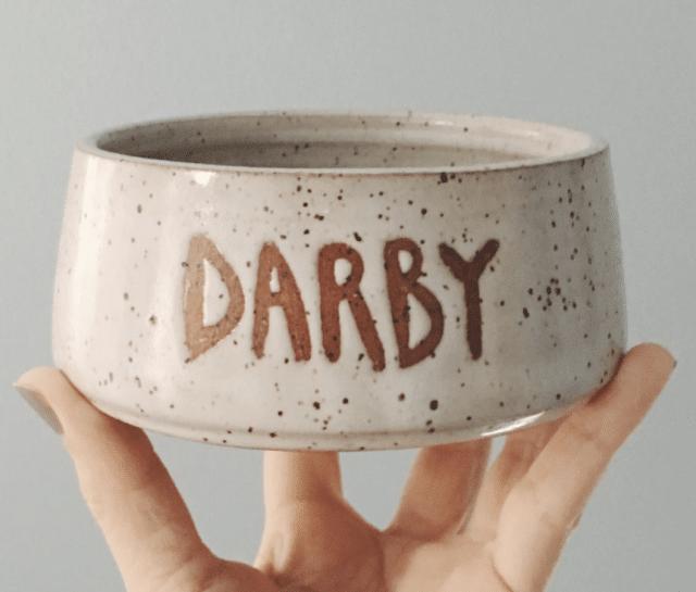 a hand holding up a custom ceramic pet bowl