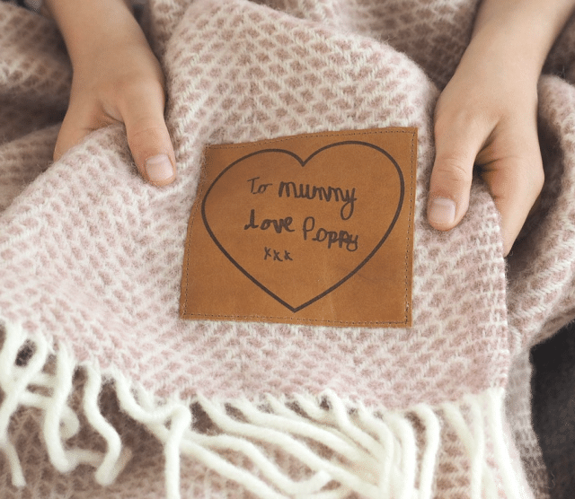 custom throw blanket with handwritten leather tag and a girls hand holding it
