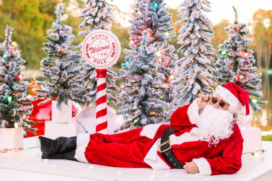 santa laying next to the pool with christmas trees