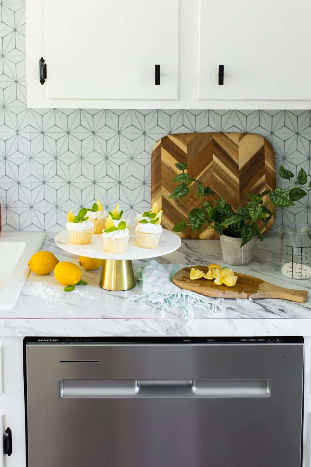photo of the lemon cupcakes being garnished in the kitchen by top Houston lifestyle blogger Ashley Rose of Sugar & Cloth