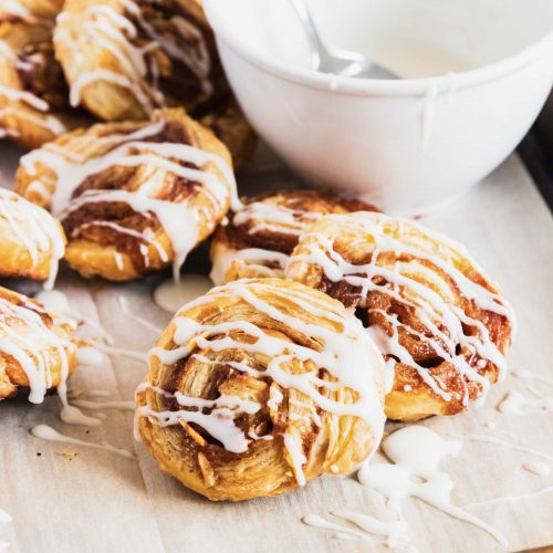 photo of homemade puff pastry cinnamon rolls with vanilla glaze and almonds by top Houston lifestyle blogger Ashley Rose of Sugar & Cloth