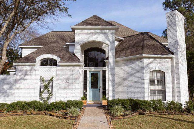 a horizontal photo of painted white exterior brick house