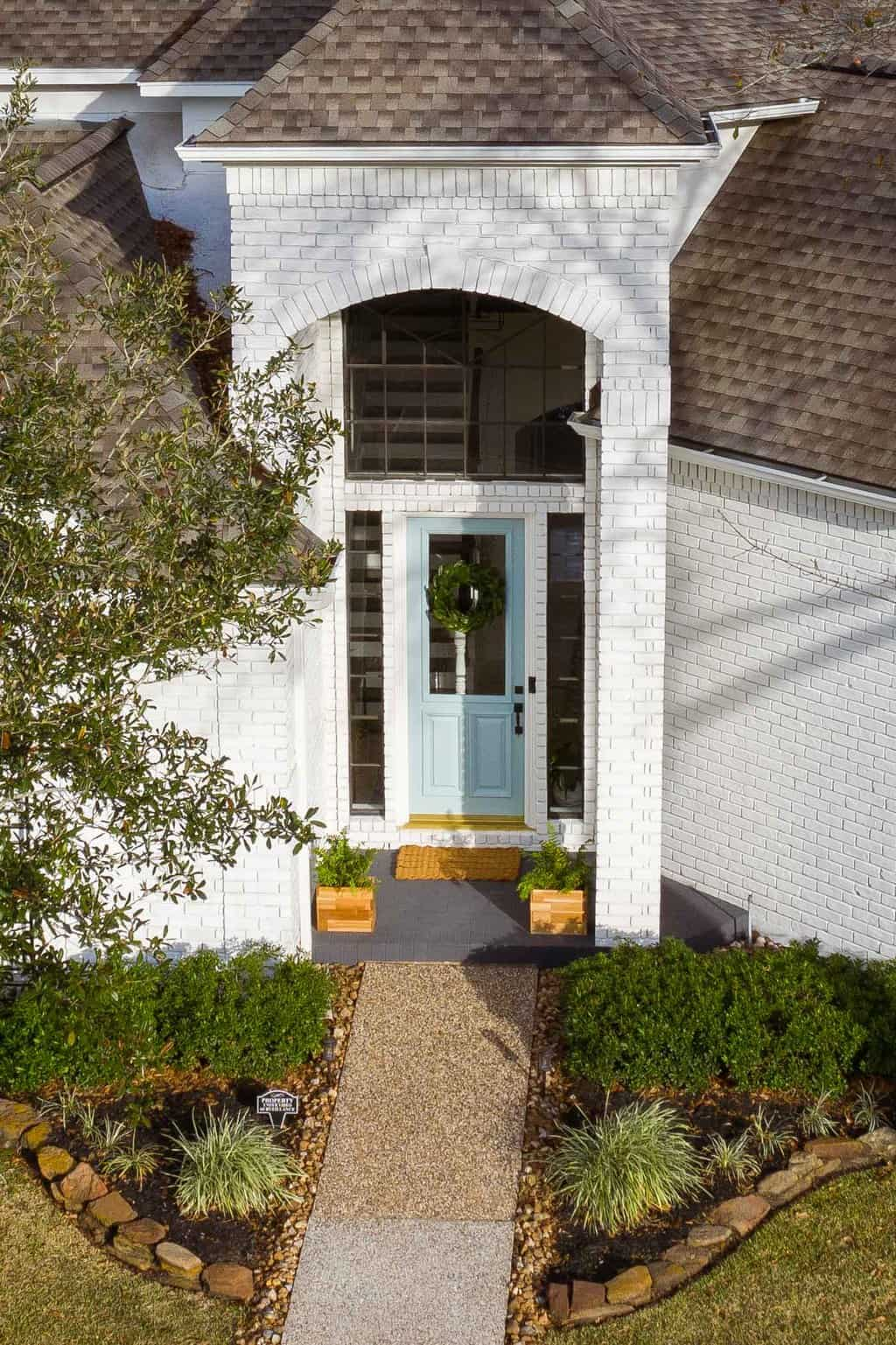 drone photo of an updated exterior brick house entrance