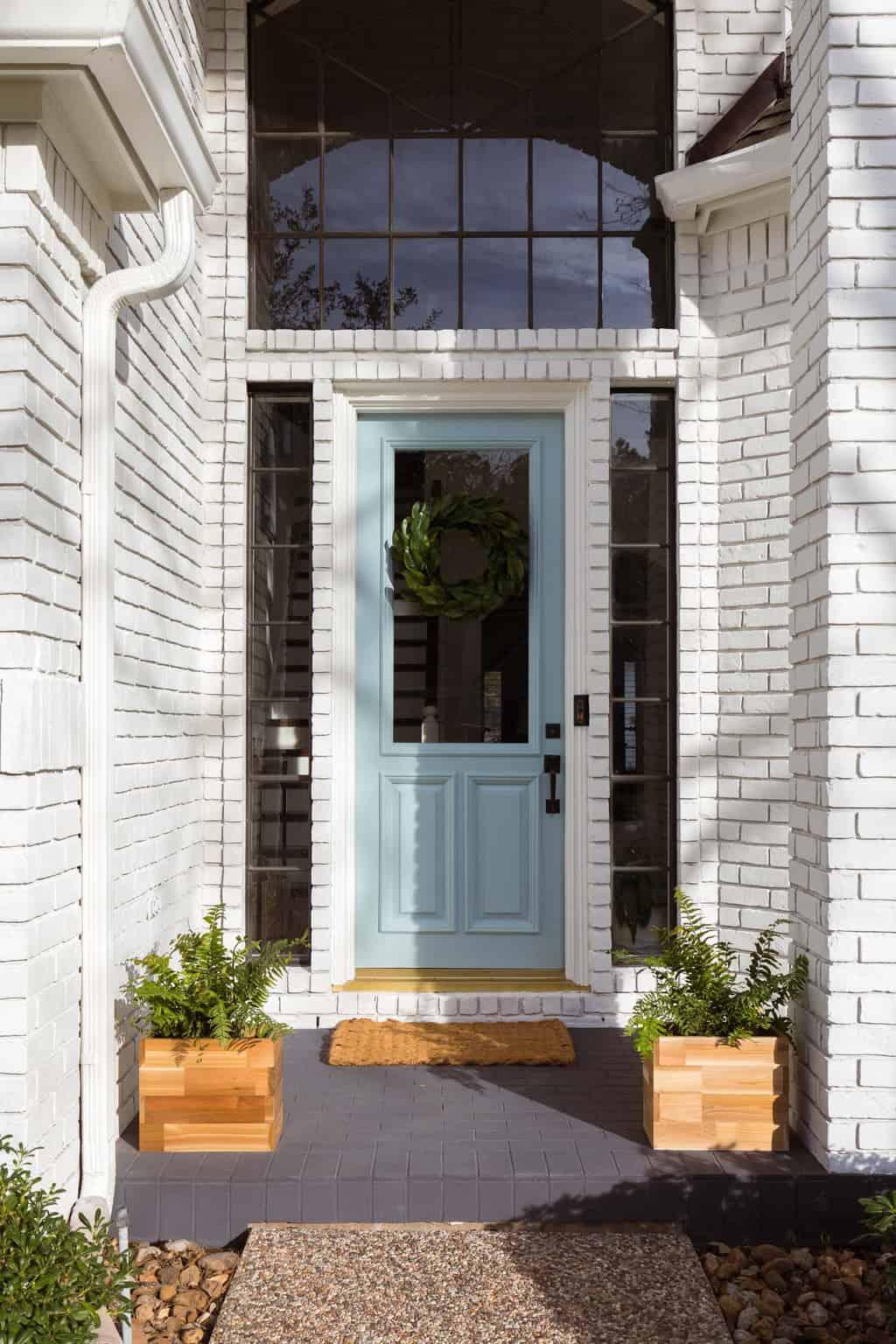a limewash painted brick front porch and white brick exterior