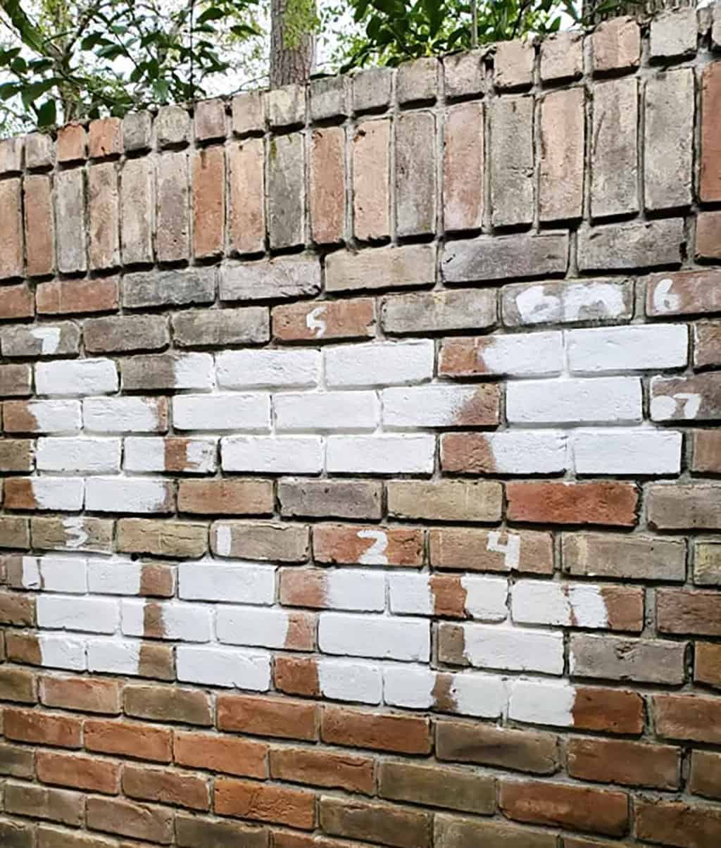 painted white color samples on a brick wall