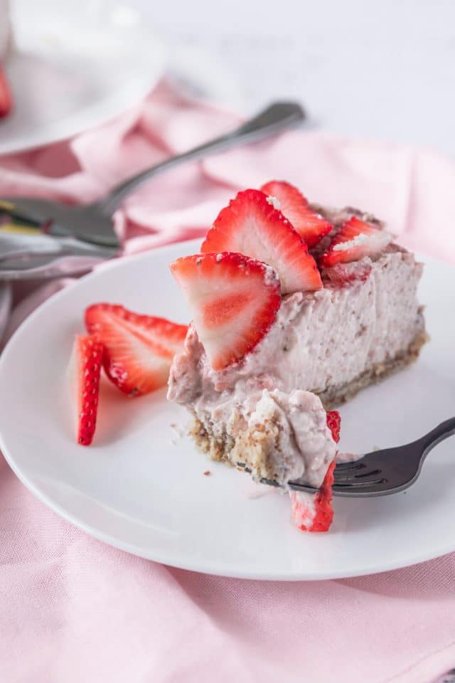 close up photo of a slice of keto strawberry cheesecake by top Houston lifestyle blogger Ashley Rose of Sugar & Cloth