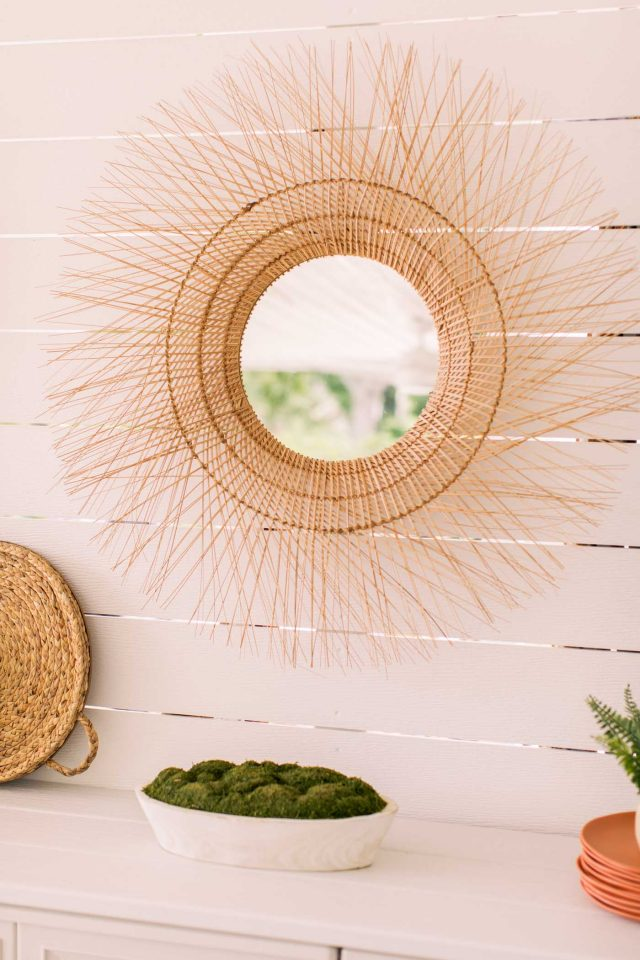 rattan wicker mirror on a shiplap wall