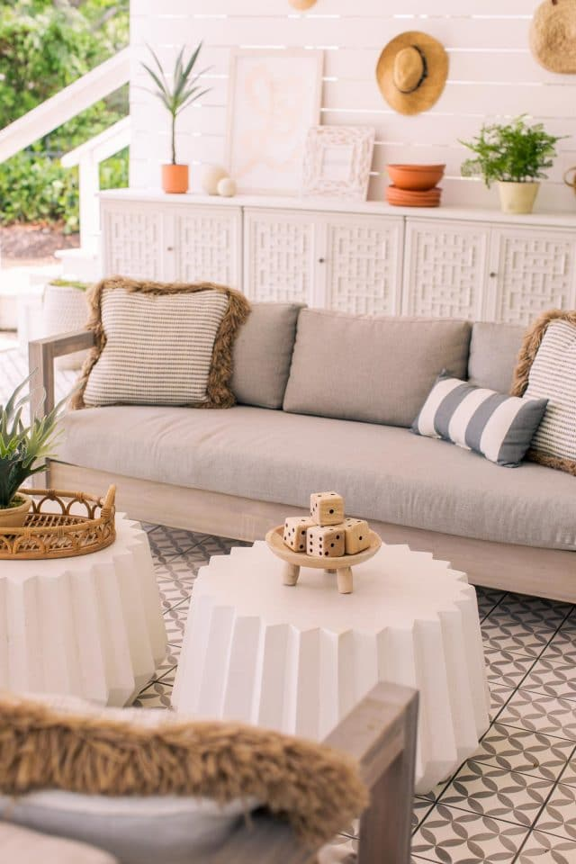 two white geometric concrete tables in front of an outdoor sofa