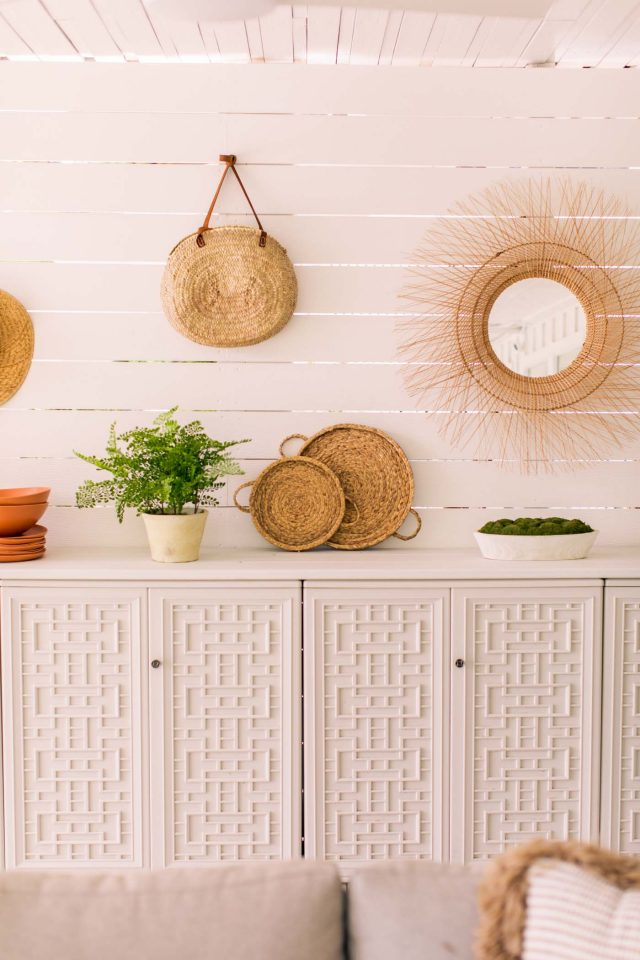 mirrors and rattan weavings on shiplap wall