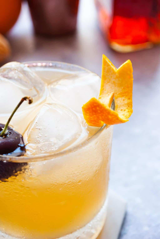 How To Make Amaretto Sour - a close up shot of Amaretto Sour with a decorative orange peel.