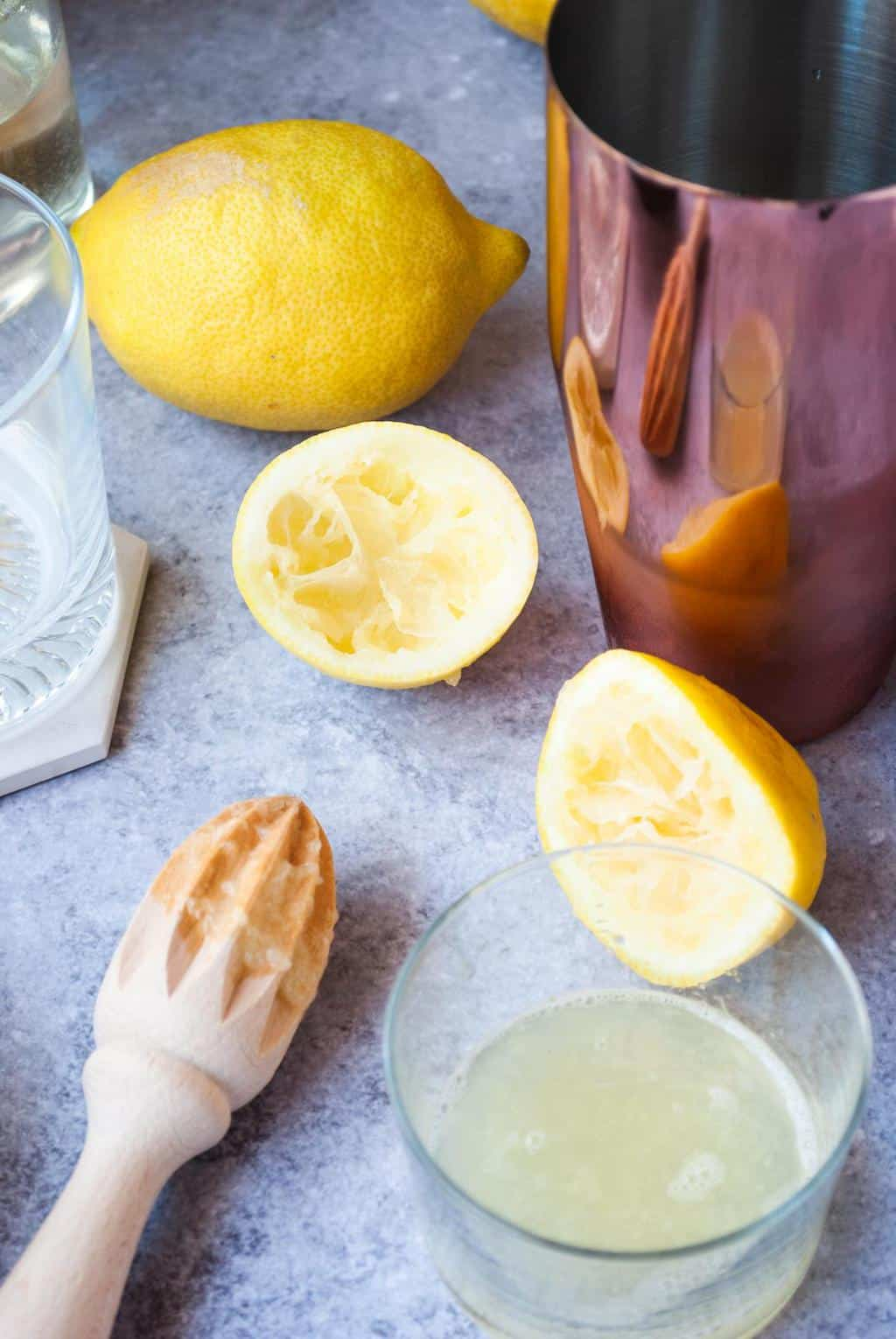 Amaretto Sour Ingredients - a photo of a freshly squeezed lemon placed inside a glass.