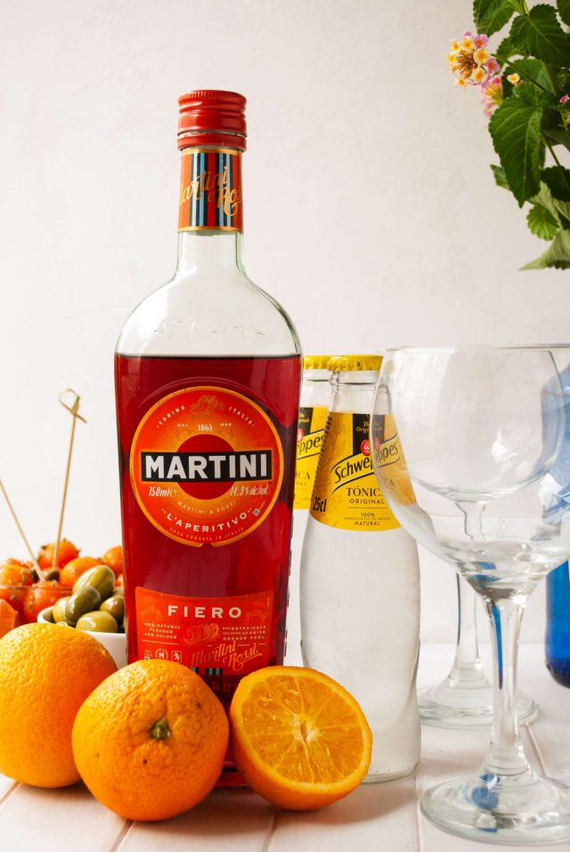 orange martini - oranges, bottle of martini fiero and a tonic water near a glass