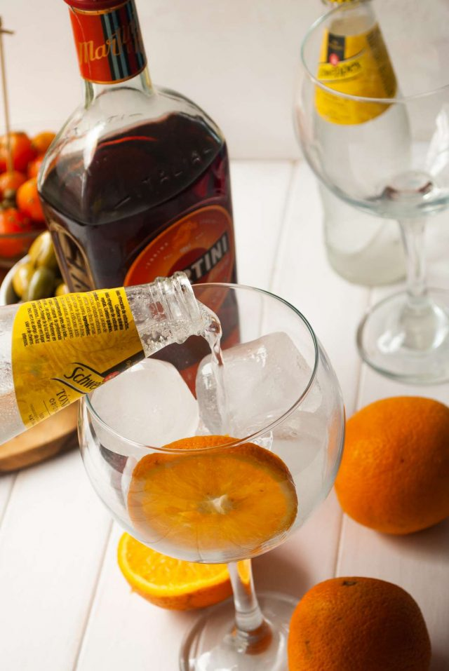 martini wiki - tonic water being poured on a glass full of ice and a single slice of orange