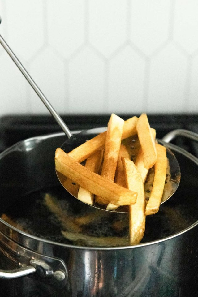 how to make homemade french fries - golden french fries being scooped out of the pan